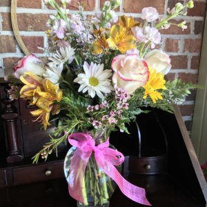 Fresh seasonal flowers professionally arranged in a glass vase